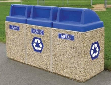 Image taken of a 3-station recycling center, set up in a park. Blue lids are placed for each of the three bins. A label exists on each bin for glass, plastic, and metal. Two recycling placards are on the side as well.